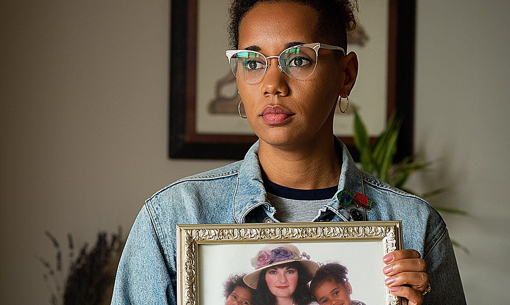 African-American woman with denim jacket and wearing glasses. Looking off to the right of the camera. Holding a photo of her mother and Alica's siblings when they were children.