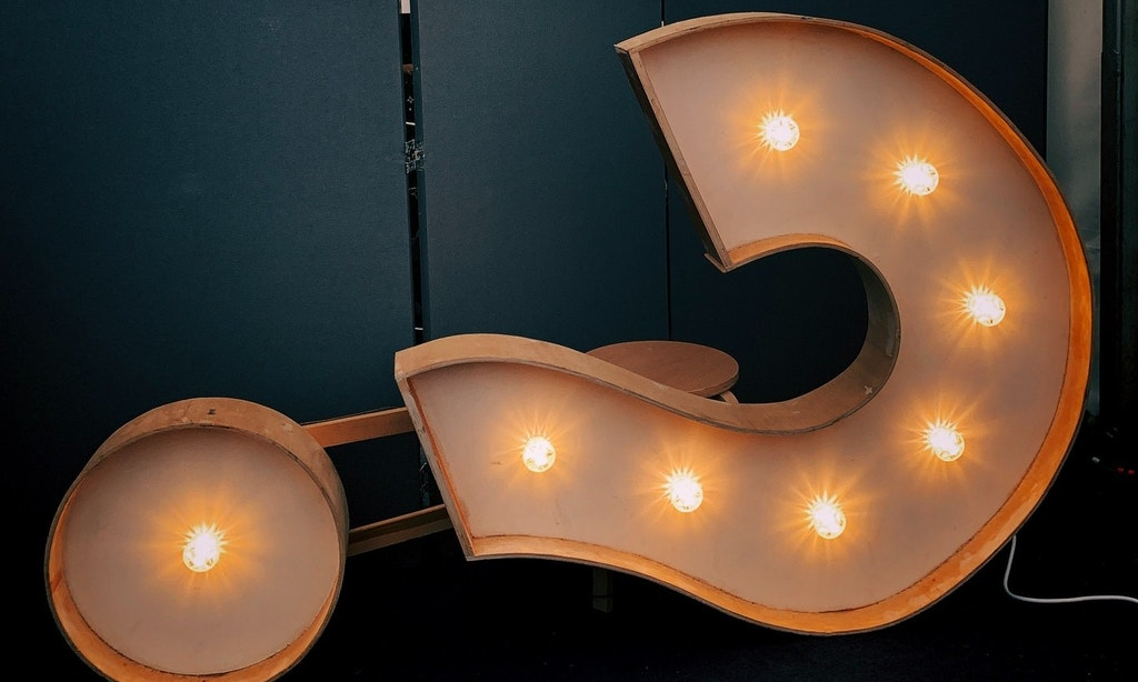 Art piece of question mark on its side. Lights run through the center of the question mark.
