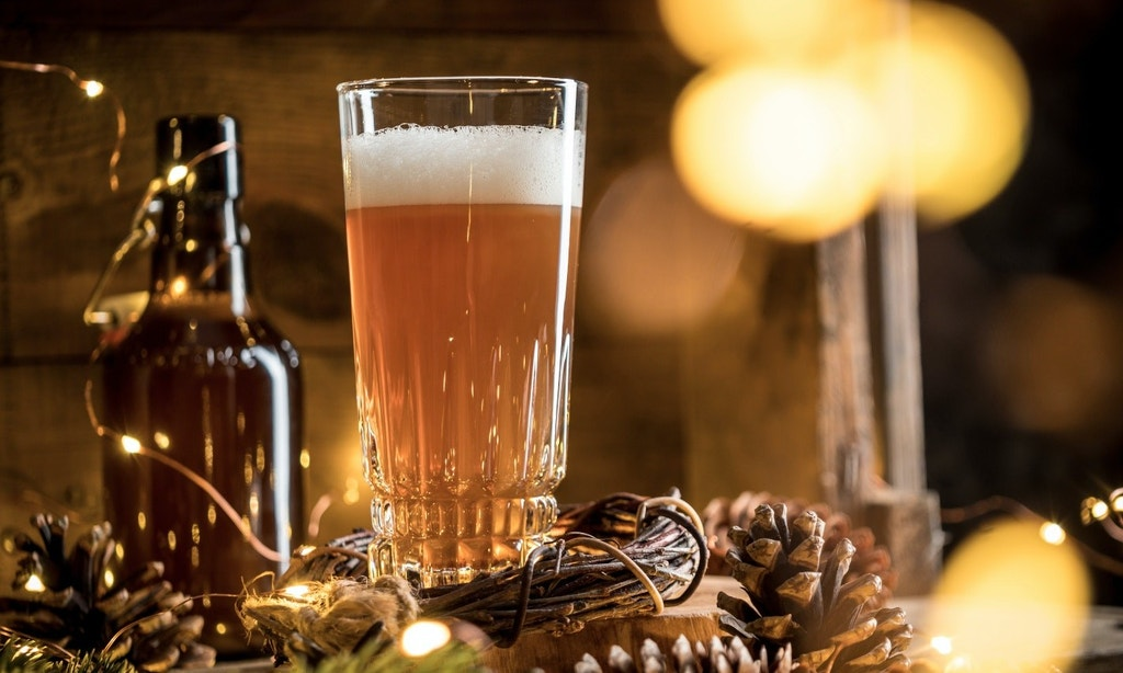 Glass of beer with foam on table with string lights and soft lights in the background.