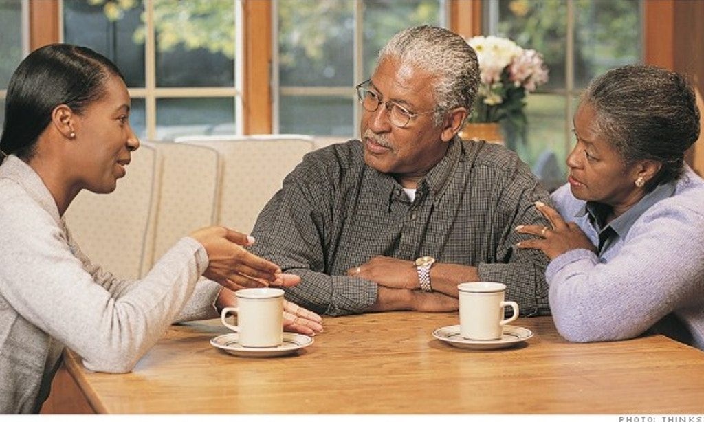 Image of three African-American family members sitting at table with coffee cups. Middle-aged daughter is talking to her elderly mother and father.