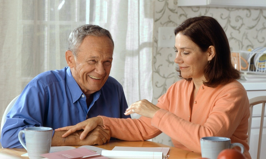 Middle-aged woman having a conversation with her smiling father.