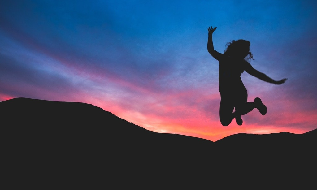 Silhouette of woman jumping in the air. Background is a silhouette of mountains wit a blue and pink sunset sky.